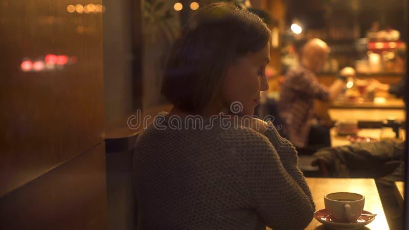 Schuwe eenzame vrouwenzitting in koffie, die over persoonlijk geluk, melancholie dromen royalty-vrije stock afbeelding