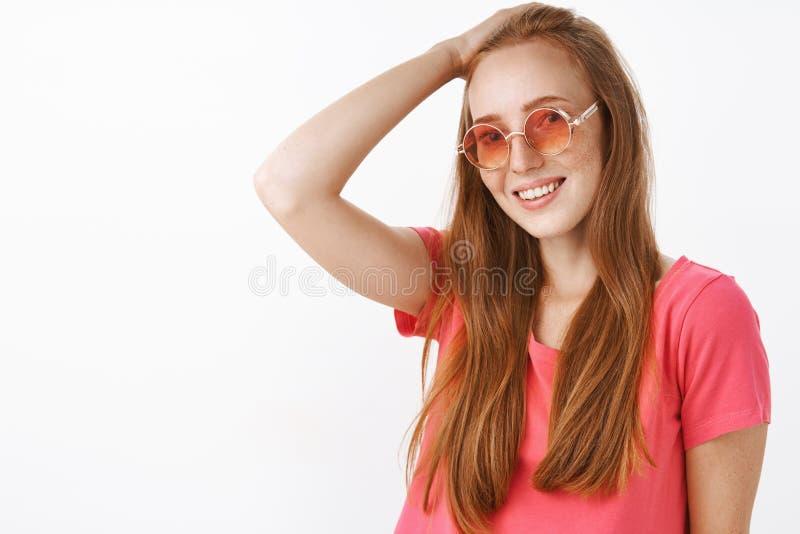 Schuwe en tedere charmante roodharigedame die met sproeten in in zonnebril en roze blouse haar behin met hand kammen stock fotografie