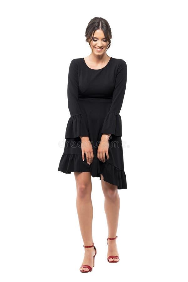 Schuwe jonge Spaanse vrouw in zwarte flounce en kleding die neer lachen eruit zien stock foto's