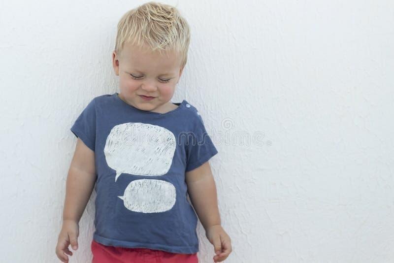 Schuwe smirking blondepeuter tegen witte muur Model voor t-shirtontwerp De ruimte van het exemplaar stock afbeelding