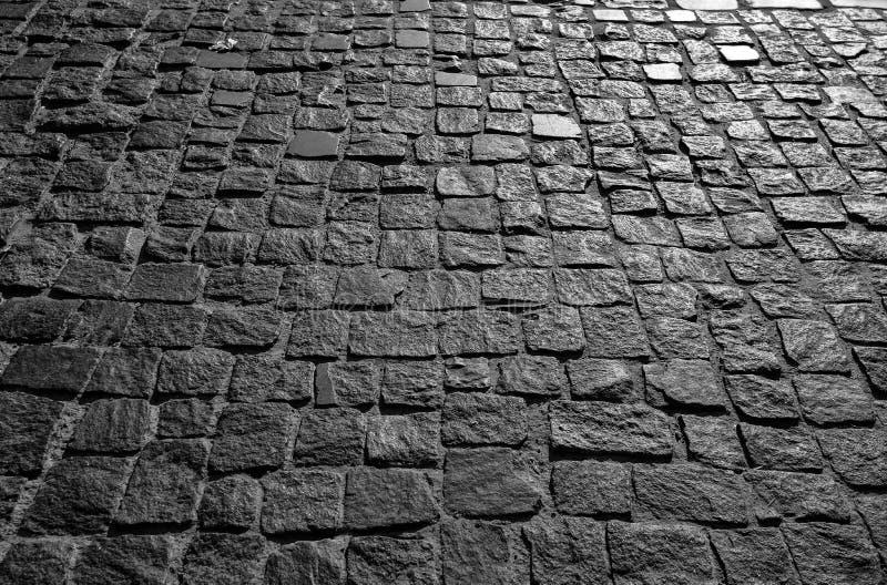 Schwärzen Sie cobbled Steinstraßenhintergrund mit der Reflexion des Lichtes gesehen auf der Straße Schwarze oder dunkelgraue Stei stockfoto