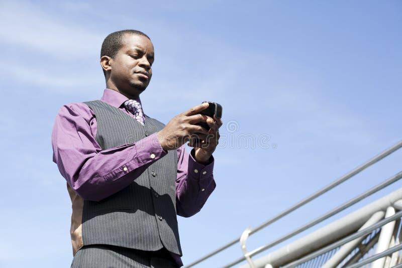 Schwärzen Sie den Geschäftsmann, der mit intelligentem Telefon arbeitet stockfotos