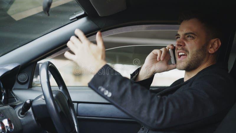 Schwörendes und Unterhaltungstelefon des betonten Geschäftsmannes beim innerhalb des Autos draußen sitzen lizenzfreie stockfotos