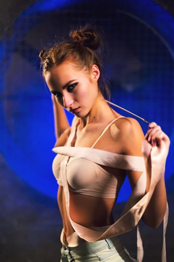 Schwüle schöne junge Turnerfrau, die mit Gymnastikband aufwirft lizenzfreies stockbild