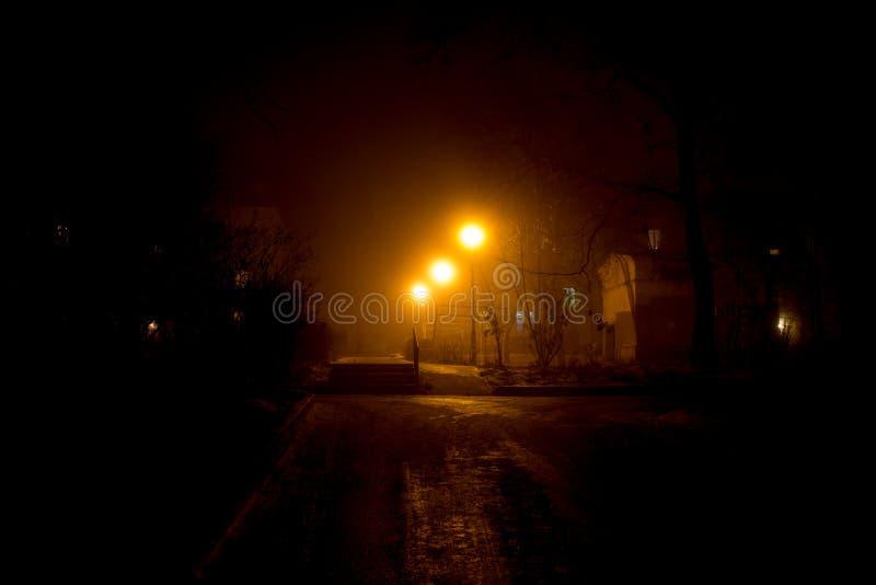 Schwach belichtet durch Straßenlaternen, der städtische Hof, starker Nebel nachts stockfoto
