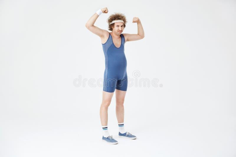 Schwacher Mann mit dem Bauch, der die Muskeln, werfend im Sportoverall zeigt auf stockbild