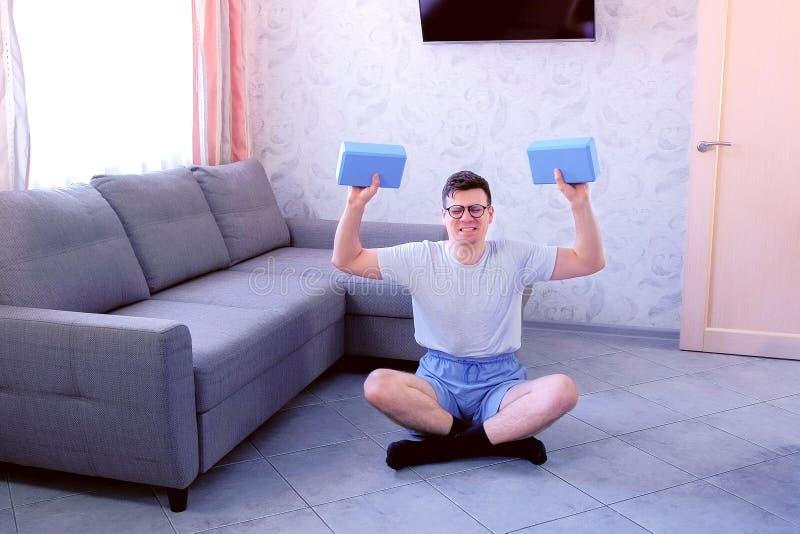 Schwacher Sonderlingsmann tut Übungen für Hände mit Yogablöcken anstelle der Dummköpfe Sportstimmungskonzept lizenzfreie stockfotos