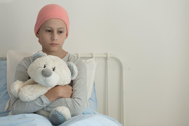 Schwaches Mädchen mit Krebs, der rosa Kopftuch trägt und Teddybären nahe bei Kopienraum umarmt lizenzfreie stockfotografie