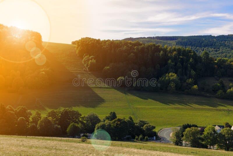 Schwalefeld, Niemcy - Lesiści wzgórza i luksusowa zielona dolina w ciepłym popołudniowym słońcu z obiektywem migoczą fotografia stock