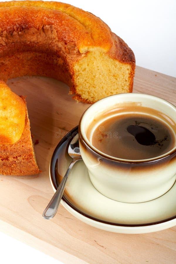 Schwammkuchen mit dem Tasse Kaffee und dem Löffel auf hölzerner Platte lizenzfreie stockfotografie
