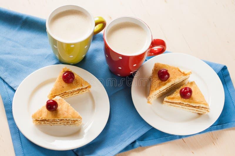 Schwammkuchen mit Kirschen auf einer Platte und einem Tasse Kaffee lizenzfreie stockfotografie