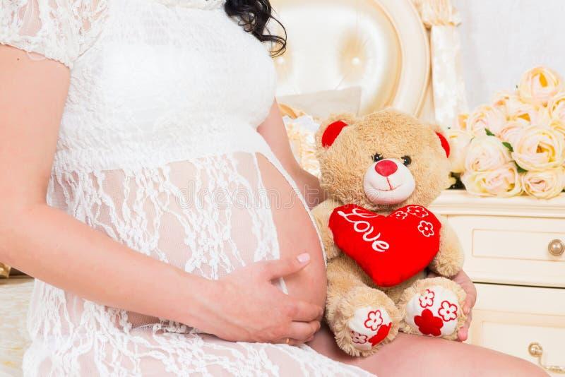 Schwanger in einem weißen Spitzekleid mit Teddybären stockbild