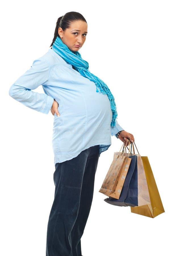 Schwanger am Einkauf mit Rückenschmerzen lizenzfreies stockbild