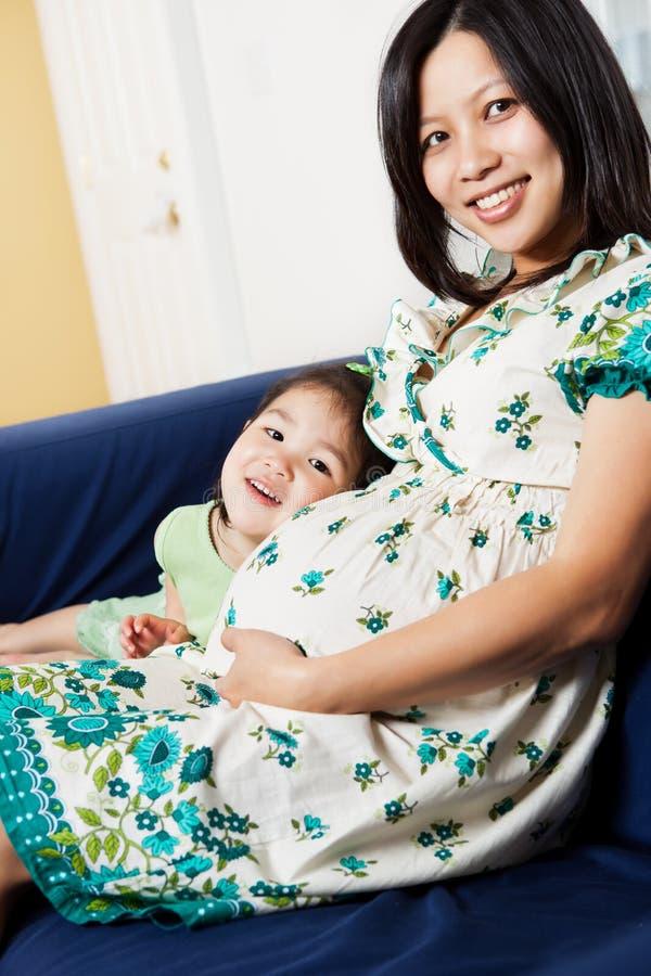Schwangere asiatische Mutter und ihre Tochter stockfotografie
