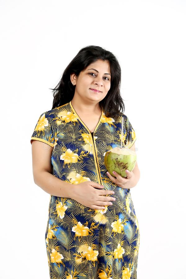 Schwangere Damenhand berührt Bauch und andere Hand hält Kokosnusswasser lizenzfreie stockfotos