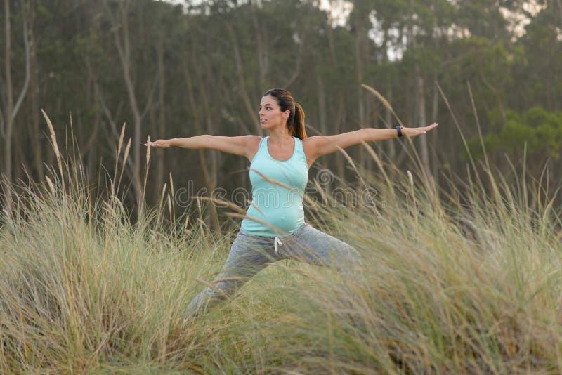 Schwangere Eignungsfrau, welche die Yogaübung im Freien tut stockfoto