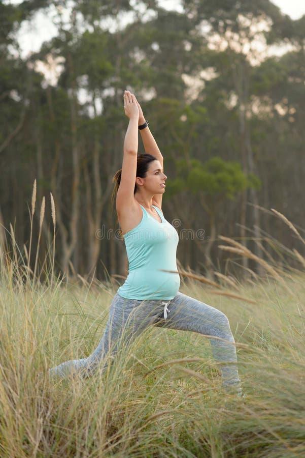 Schwangere Eignungsfrau, welche die Yogaatemgymnastik im Freien tut lizenzfreie stockfotografie