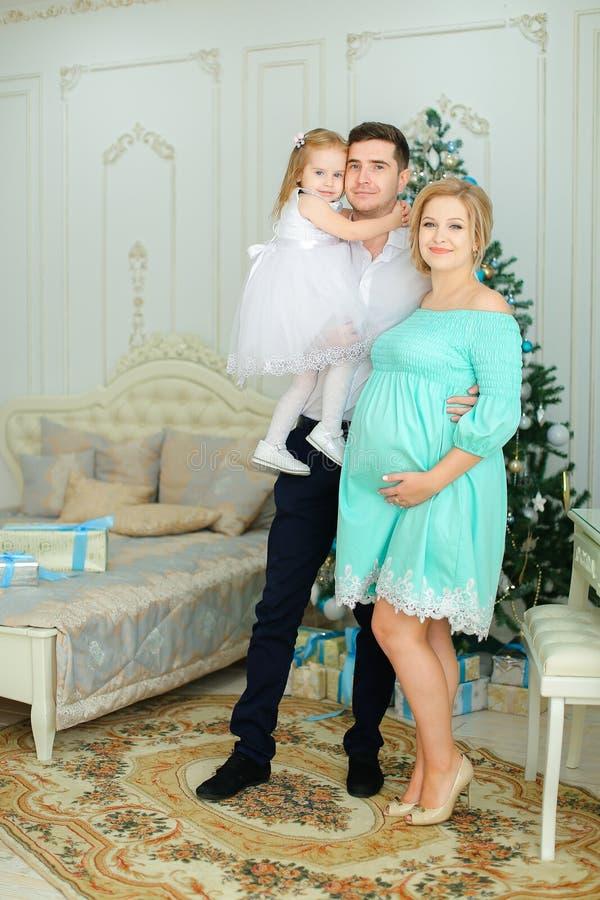 Schwangere europäische Frau, die das blaue Kleid steht mit Ehemann und kleiner Tochter nahe Weihnachtsbaum trägt stockfoto