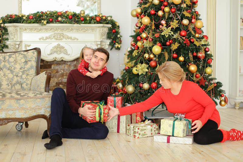 Schwangere europäische Frau, die mit Mann und kleiner Tochter nahe Weihnachtsbaum und gifting Geschenken sitzt stockfoto