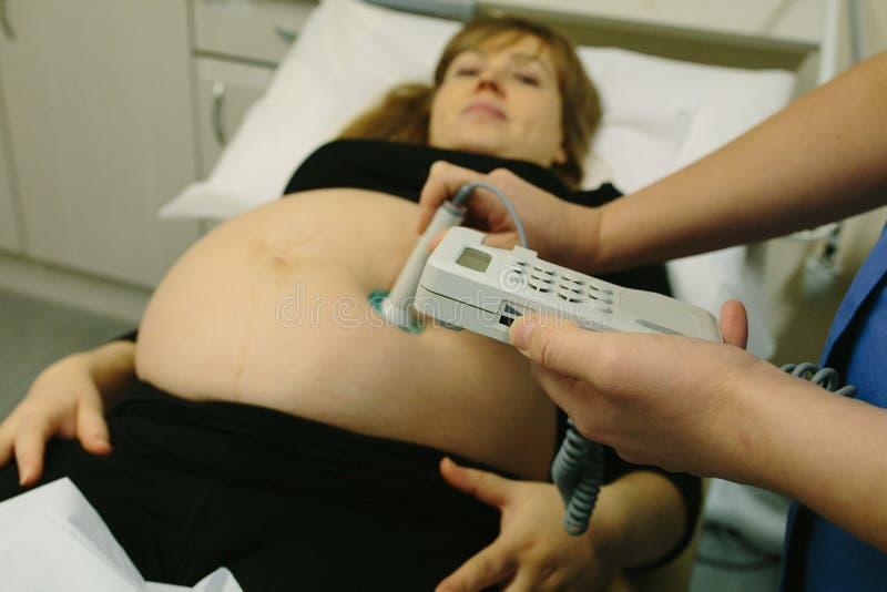 Schwangere Frau überprüft von der Hebamme stockfotografie