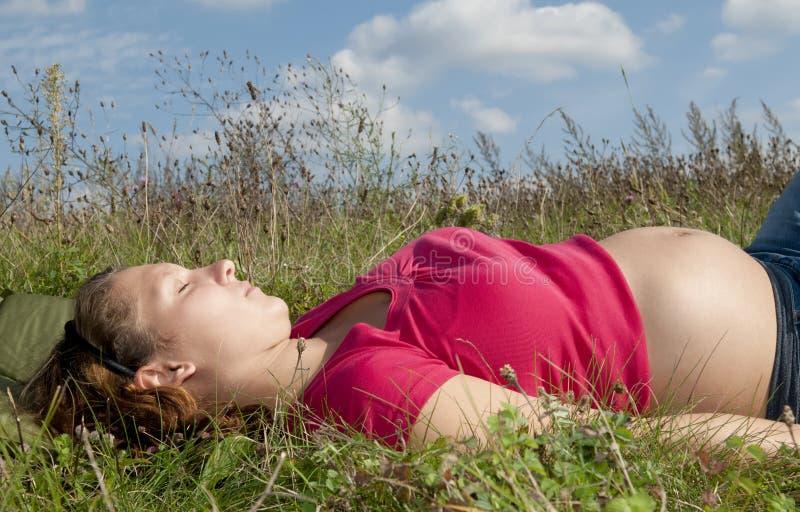 Schwangere Frau auf einer Wiese lizenzfreie stockfotos