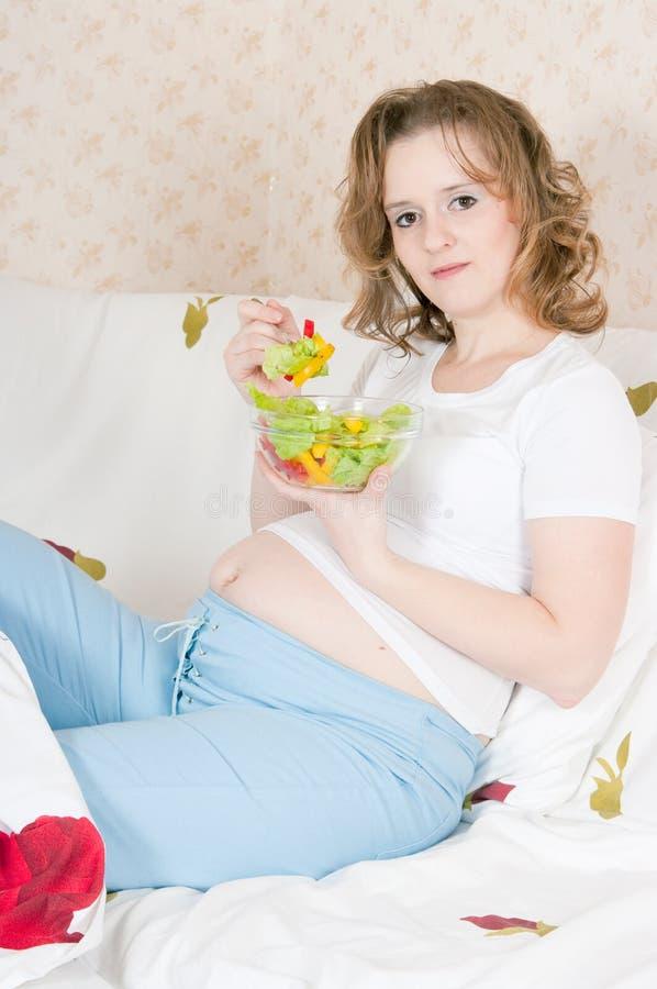 Schwangere Frau beim Bettessen lizenzfreies stockfoto