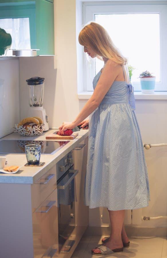 Schwangere Frau bereiten gesunde Mahlzeit in der Küche vor stockfotografie