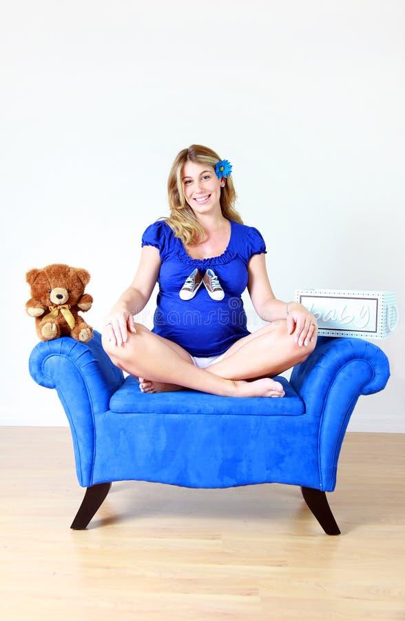 Schwangere Frau in der blauen Kleidung lizenzfreie stockfotografie