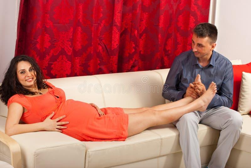 Schwangere Frau der Ehemannmassage lizenzfreie stockbilder