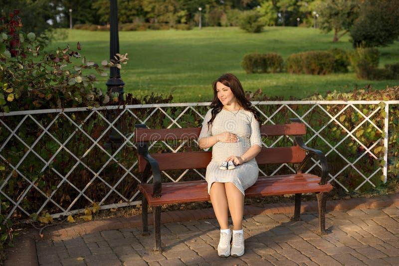 Schwangere Frau der Junge, die auf Bank in den Park- und Griffturnschuhen für neugeborenes sitzt lizenzfreie stockfotografie