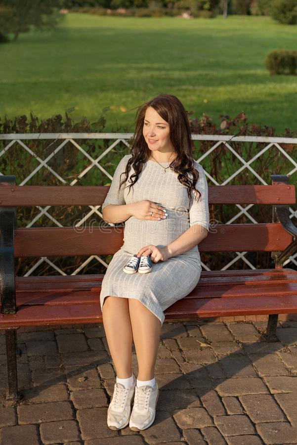 Schwangere Frau der Junge, die auf Bank in den Park- und Griffturnschuhen für neugeborenes sitzt stockfoto