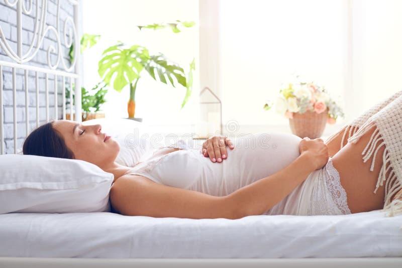 Schwangere Frau der Junge, die auf Bett im weißen Schlafzimmer schläft lizenzfreie stockfotografie