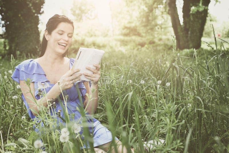 Schwangere Frau der Junge, die auf Gras und Lesebuch sitzt lizenzfreie stockbilder