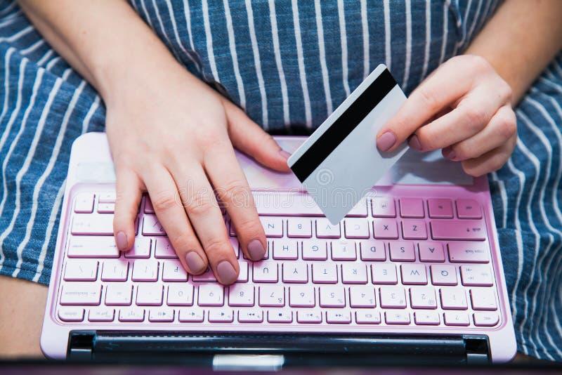 Schwangere Frau der Junge, die online mit Laptopkreditkartenahaufnahme kauft lizenzfreie stockfotografie
