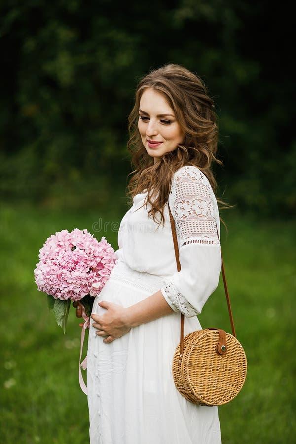 Schwangere Frau der Junge, die sich draußen im Park, gesundes pregnanc entspannt lizenzfreies stockfoto