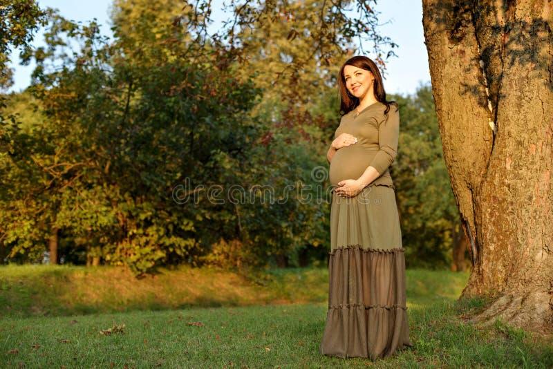 Schwangere Frau der Junge in Erwartung eines Babys, das in einem Park in der Sonne steht, strahlt aus stockfotografie