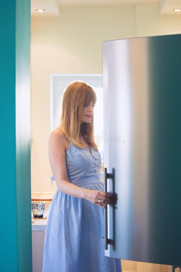 Schwangere Frau der Junge im Küchenblick im Kühlschrank lizenzfreies stockfoto