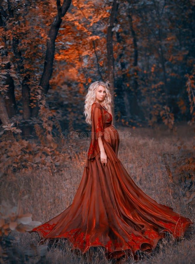 Schwangere Frau der Junge mit dem blonden gelockten Haar Kleid des langen hellen Flatterns im roten Scharlachrot, stehend im Wald stockfotos