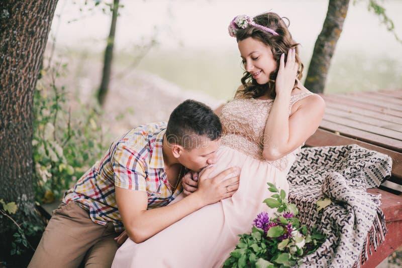 Schwangere Frau der Junge mit ihrem Ehemann, der nahe See sitzt lizenzfreies stockfoto