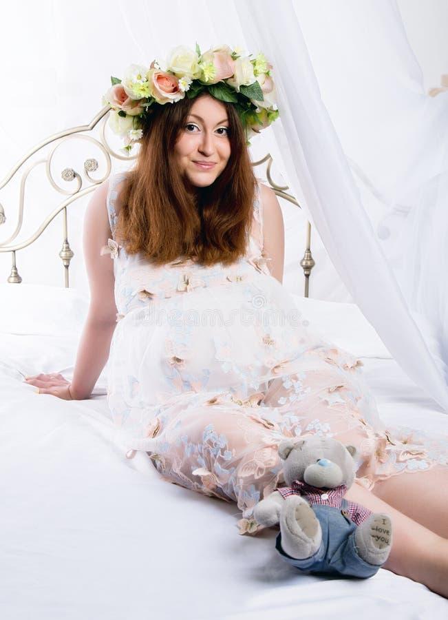 Schwangere Frau der schönen Rothaarigen liegt auf einem Bett zu Hause Schwangerschaft, Leute und Erwartungskonzept lizenzfreie stockfotografie