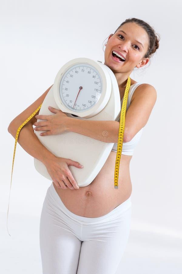 Schwangere Frau des Asiaten, die eine Gewichtsskala hält stockbilder