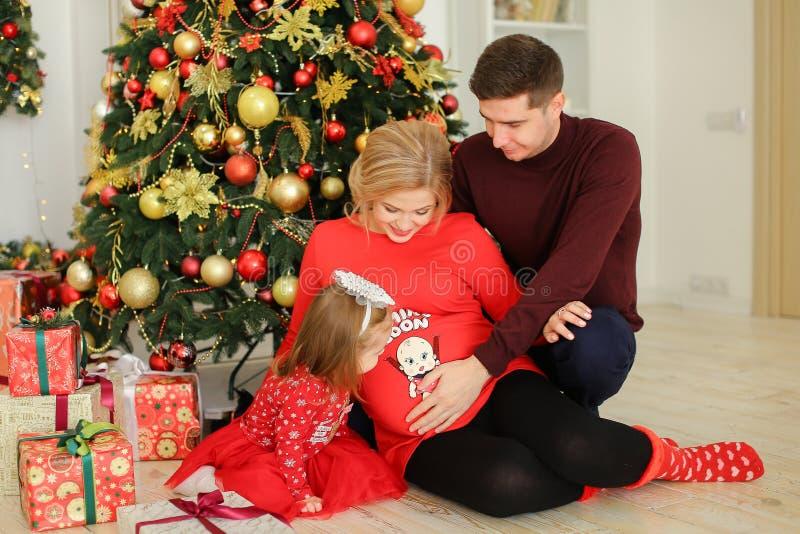 Schwangere Frau des Europäers, die mit dem Ehemann umarmt Bauch und kleine Tochter nahe Geschenken unter Chistma-Baum sitzt stockbilder