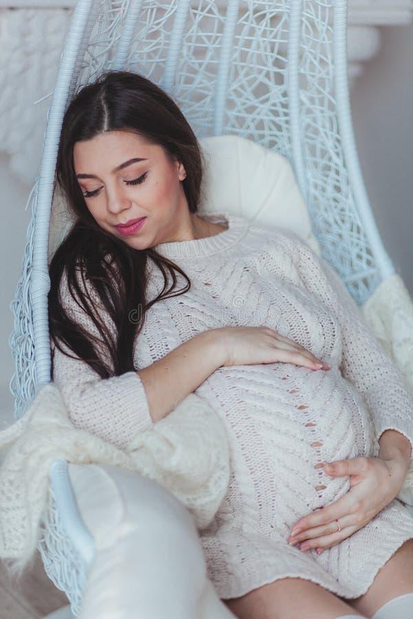 Schwangere Frau des glücklichen Brunette, die in hängendem Kokonstuhl schläft Tragende Weiß gestrickte Strickjacke lizenzfreie stockbilder