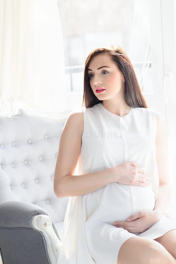 Schwangere Frau des schönen jungen Brunette im weißen Kleid lizenzfreie stockfotografie