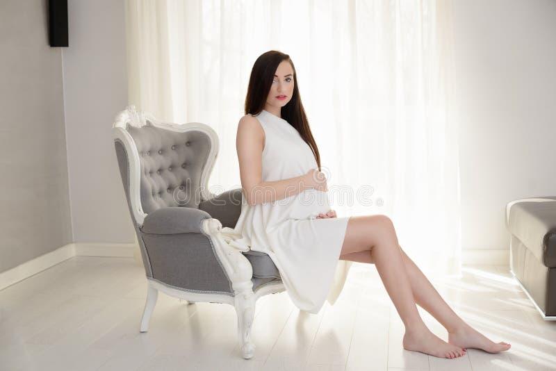 Schwangere Frau des schönen jungen Brunette im weißen Kleid stockbild
