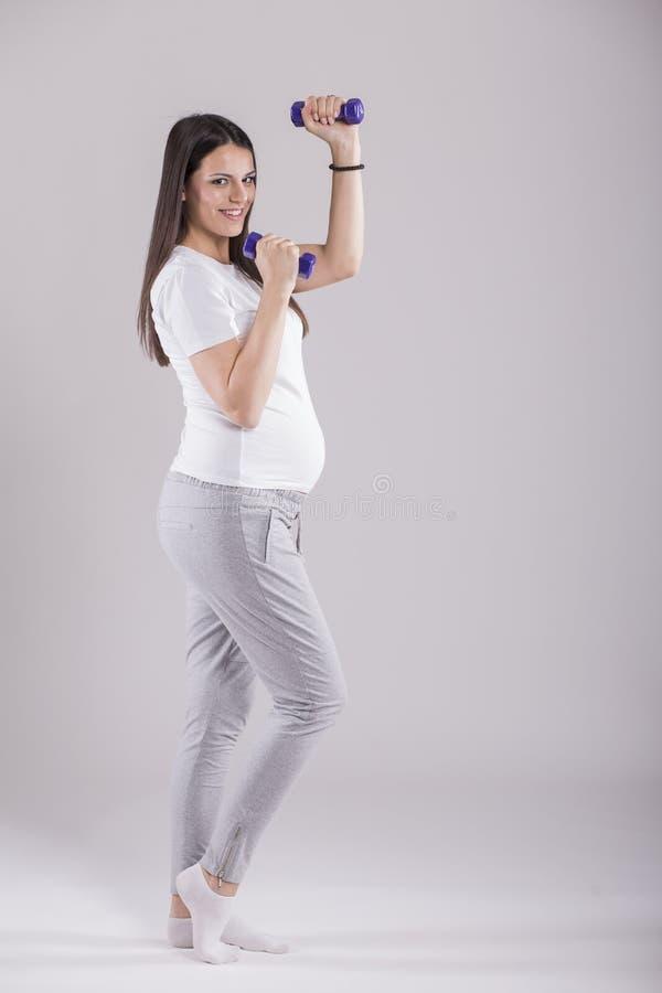 Schwangere Frau, die Übung tut stockbilder