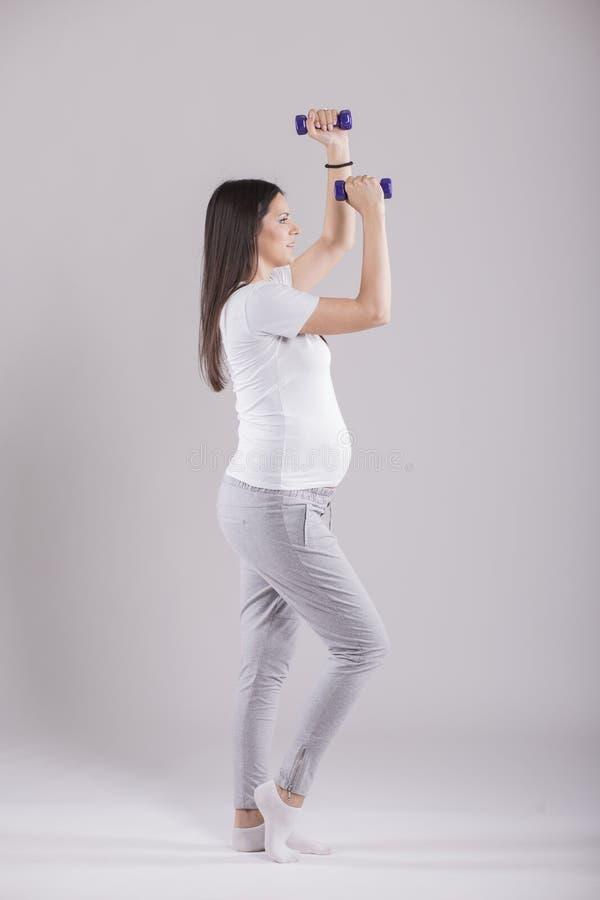 Schwangere Frau, die Übung tut stockbild