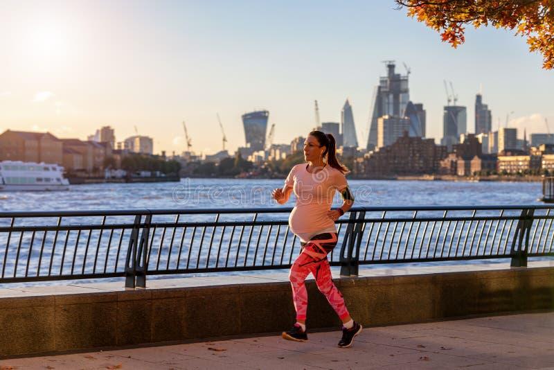 Schwangere Frau, die auf dem Flussufer in London trainiert stockfotos