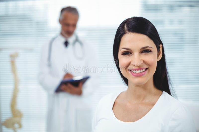 Schwangere Frau, die auf Doktor einwirkt stockfotos