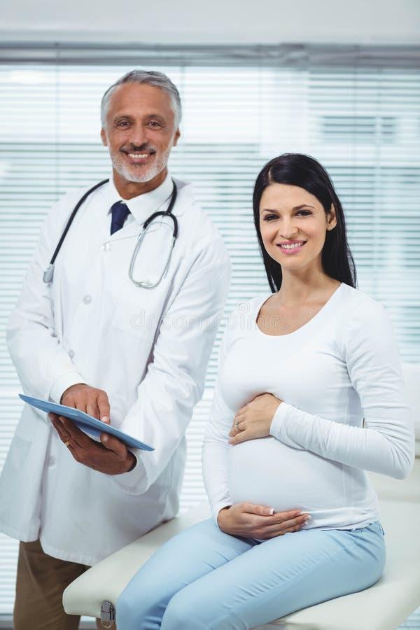 Schwangere Frau, die auf Doktor einwirkt stockfotografie